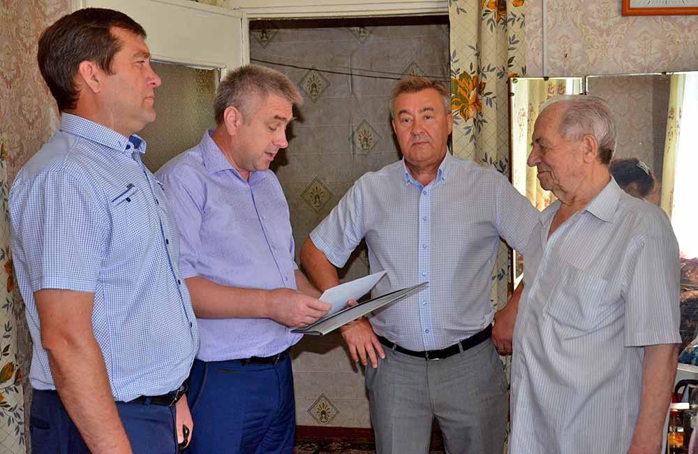 Анатолия Нестерова (справа) с днем рождения поздравляют заместители главы района Олег Малыхин (слева), Александр Михалин (второй справа), а также представитель Центра соцзащиты Александр Щедрин.
