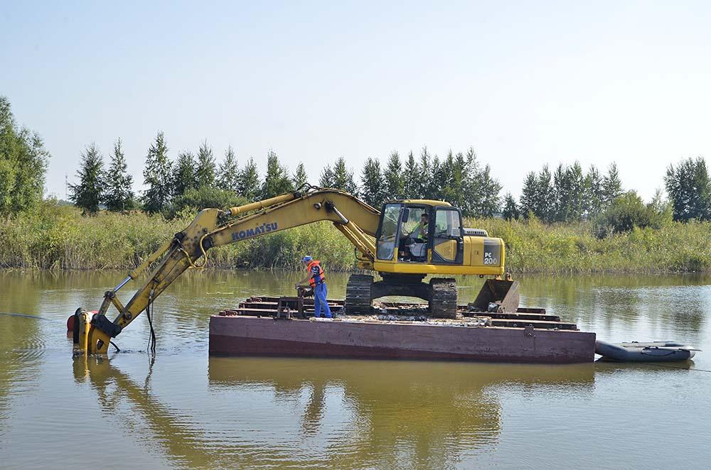 Сначала подрядчики очистили берега от зарослей камыша и кустарника. Сейчас тяжелая техника, размещенная на плавучем понтоне, забирает ил со дна водоема.